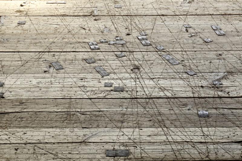 Surface scarifiée, constellée de repères en laiton du plancher bois sur lequel était dessiné les coques de bateau.   - Salle à tracer, Nantes